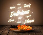 Food plate with delicious and tasty glowing writings on wood deck