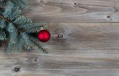 Red Ball Christmas Ornament On Pine Tree Branch With Rustic Wood