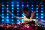 Attractive young Dj mixing records with colorful lights