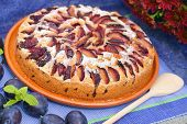 A whole plum cake on a blue table