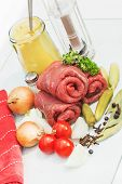 Three raw beef olives with ingredients for cooking