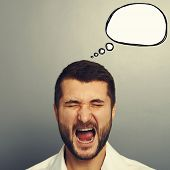 portrait of screaming man with empty speech bubble over grey background