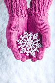 Woman hands in light pink knitted mittens with sparkling wonderful snowflake on a white snow background. Winter and Christmas concept.
