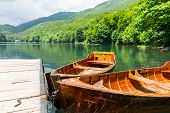 Wooden boats at pier on mountain lake