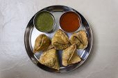 Indian snack called samosa served with sweet & sour ketchup and spicy chilly chutney