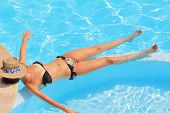The slender young girl has a rest and sunbathes in clear and transparent water of the pool