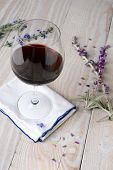 A glass of red wine on a napkin and a white rustic wood table. Flowers and petals are scattered on t