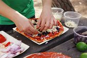 making hand made pizza with olives and tomatoes on wooden table on picnic