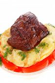 fresh roast beef meat chunk in transparent bowl over baked potatoes and tomatoes served with fill is