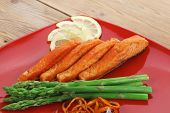 grilled salmon slices with asparagus lemon fried orange peel and cutlery on red plate over wooden ta
