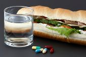 Glass Of Water, Pills And Two Hot Dogs With Various Ingredients.