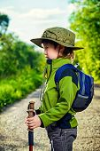 Portrait of a cute 7 years old boy in tourist clothes posing outdoor. Summer day.
