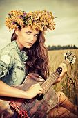 stock photo of hippies  - Romantic girl in a wreath of wild flowers travelling with her guitar - JPG