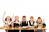 Schoolchildren sit together at the table and raise their hands during the lesson. Isolated over whit