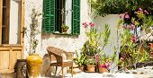 Traditional courtyard with chairs and a lot o flowers in old village in Mallorca island, Spain