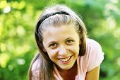 Portrait of a smiling beautiful young girl on a green background