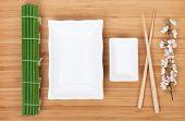 Empty plates, chopsticks and sakura branch over bamboo table