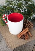 Empty cup for mulled wine, spices and fir tree on wooden table