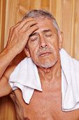 Senior man sweating with towl in hotel sauna in his holidays