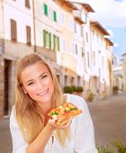 Portrait of attractive young girl eating tasty pizza in the Italy, sitting in the outdoors restauran