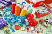 Spools Of Colorful Thread, Buttons, Fabrics, Measuring Tape, Pincushion And Measuring Tape