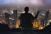 Silhouette of businessman sit on chair and hold a cigar, looking the harbor of Victoria at Hong Kong