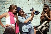 Urban girls have fun with vintage photo cameras outdoor near grunge wall, filtered