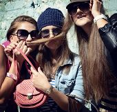 Girls having fun together outdoors and making moustache of hair, lifestyle theme