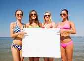 summer vacation, holidays, travel, advertising and people concept - group of smiling young women wit