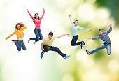 happiness, freedom, ecology, friendship and people concept - group of smiling teenagers jumping in a