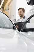 Maintenance engineer holding tablet PC while examining car in repair shop