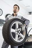 Young maintenance engineer carrying tire in automobile store