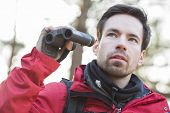 Young male hiker with binoculars in forest