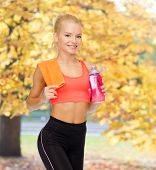 sport, exercise and healthcare concept - sporty woman with orange towel and water bottle