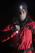 Portrait of confident male hiker with flashlight at night