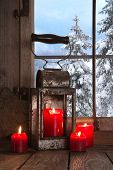 Old Wooden Windowsill Decorated With Four Red Christmas Candles And A Old Tin Lantern.