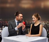 restaurant, couple and holiday concept - excited young woman looking at boyfriend with gift box at r