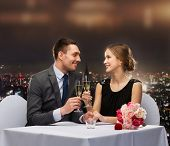 restaurant, couple and holiday concept - smiling couple with glass of champagne looking at each othe