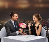 restaurant, couple and holiday concept - smiling man giving flower bouquet to woman at restaurant