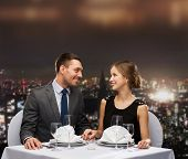 restaurant, couple and holiday concept - smiling couple looking at each other at restaurant