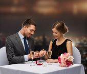 restaurant, couple and holiday concept - smiling man putting on finger engagement ring at restaurant