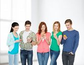 education and modern technology concept - smiling students with smartphones