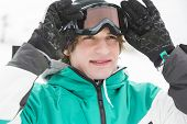 Handsome young man wearing ski goggles outdoors