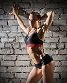 Young muscular woman on grey brick wall (dark version)