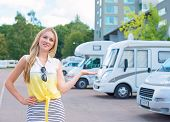 stock photo of campervan  - Beautiful young woman offers campervans at shop - JPG