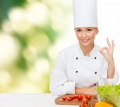 cooking and food concept - smiling female chef with vegetables showing ok sign