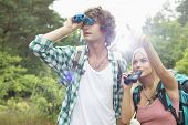 Male hiker using binoculars while woman showing him something in forest