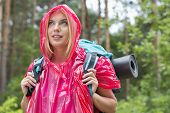 Beautiful backpacker in raincoat looking away at forest