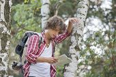 Backpacker reading map while leaning on tree trunk in forest