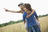 Woman showing something while enjoying piggyback ride on man in field